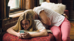 Teen Girl Uses Her Smart Phone, While Her Sleepy Sister Snuggles Up To Her Stock Footage