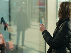 Woman taking photo of handbags on shop window with cellphone NTSC Stock Footage
