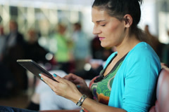 Happy woman with tablet computer waiting on the airport Stock Footage