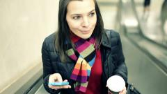 Young woman with smartphone and coffee riding escalator HD Stock Footage