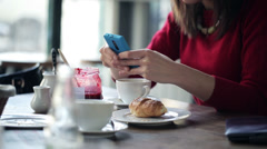 Woman hands texting on smartphone during breakfast in cafe HD - stock footage