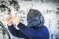Panttivanki käsiraudoissa ja pussin pään lähellä seinää Kuvituskuvat