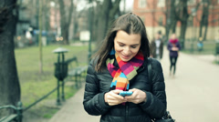 Young woman using smartphone during walk in city park HD Stock Footage