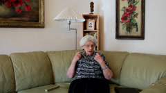 80 years old woman cools off with hand fan at home, hot day, heatwave Stock Footage