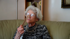 Elderly woman cooling herself with traditional wooden Asian hand fan, home, hot  Stock Footage