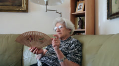 80 years old woman cooling herself with hand fan at home, hot day, heatwave - stock footage
