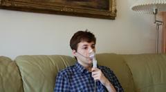 Stock Video Footage of Teenage boy using nebulizer, inhaler, asthma, respiratory diseases
