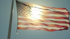 American flag, backlit by the sun, blows straight out on a windy day Stock Footage