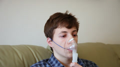 Teenage boy with bronchitis and allergies using respiratory aerosol mask Stock Footage