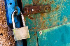 Rusty old padlock on metal door Stock Photos