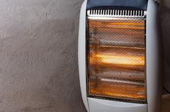 Stock Photo of A halogen or electric heater against concrete wall