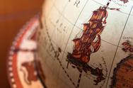 Stock Photo of Part of a globe with old ship on blurry background