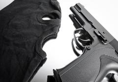 Pistol and mask of a thief over white - stock photo