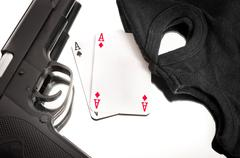 Pistol and mask of a corrup poker player Stock Photos