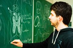 Young student showing spinal chord on green chalk board Stock Photos