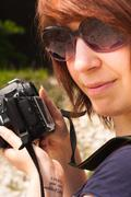 Girl with camera in warm tones - stock photo