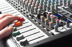 Sound mixer with hand using slider - stock photo