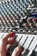 Closeup of an audio sound mixer with the hand of a man Stock Photos