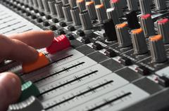 Part of an audio sound mixer with buttons and sliders and hand Stock Photos