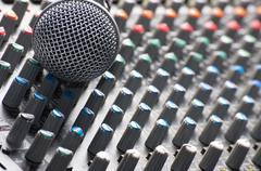 Part of an audio sound mixer with a michrophone - stock photo