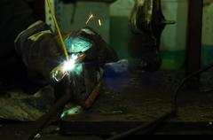 Welding in industrial enviroment with white sparks - stock photo