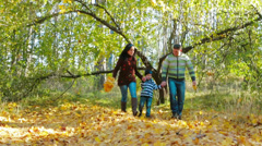 Mother, father and son walking in autumn forest. Slow motion Stock Footage