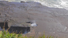 Overhead shot of ocean water coming out of a hole in the shore rock formation Stock Footage
