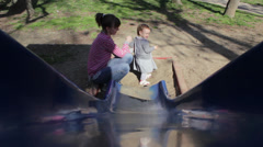 A beautiful baby girl and mother playing on the playground in the park Stock Footage