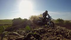 MOTOCROSS MOTORCYCLE RIDER IN EXTREME SLOW MOTION BLASTING CORNER AT SUNSET HD Stock Footage