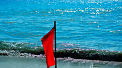 Red flag on the background of the calm sea Stock Footage