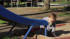 Beautiful baby girl in grey dress playing  on the playground in the park Stock Footage