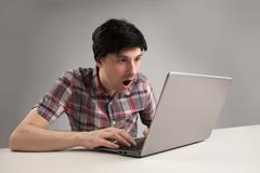 shocking man reading message on laptop computer - stock photo