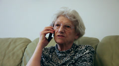 80 years old woman talking on the smart phone at home, grandma gossiping Stock Footage