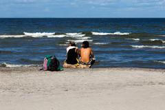 Photography of a couple seeing ocean on beach Stock Photos