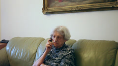 80 years old woman talking on the phone at home, grandma gossiping Stock Footage