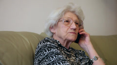 80 years old woman talking on the smart phone at home, grandma gossiping - stock footage