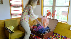 Woman take cloth from hanger flex and put into suitcase Stock Footage