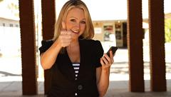 Pretty businesswoman with thumb up and mobile phone - stock footage