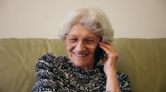 Cheerful 80 years old woman talking, laughting on the smart phone at home - stock footage