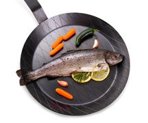 Marinated rainbow trout with lemon on frying pan Stock Photos