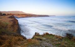 beautiful coastal landscape at sunrise with cliffs and misty glow - stock photo