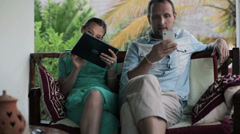 Couple with tablet computer and smartphone sitting on patio HD - stock footage