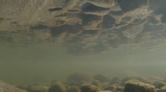 Reflections of Rocks Underwater on Surface Above Murky Shallows Stock Footage