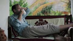 Young man on sofa drinking coffee and relaxing on patio HD - stock footage