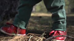 Child little legs walk in the forest in red shoes Stock Footage