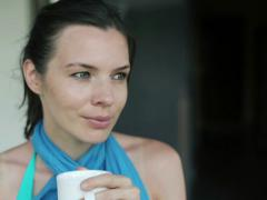 Beautiful woman drinking coffee on house patio NTSC Stock Footage
