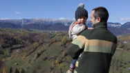 Stock Video Footage of Father and son on autumn hill admire the mountains and village
