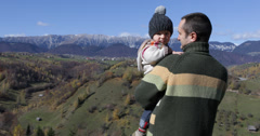 Stock Video Footage of Young father holding lovely  son admire beautiful autumn landscape, up view, 4K