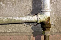 Rusted and leaking household water pipe Stock Photos