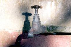Outdoor garden tap mounted on brick wall Stock Photos